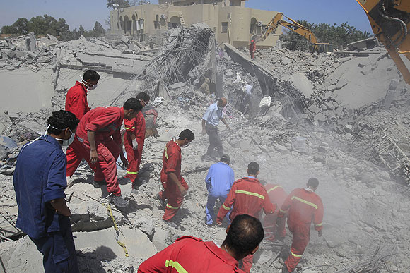 Firefighters search for survivors at a compound belonging to Khweldi Hamedi.