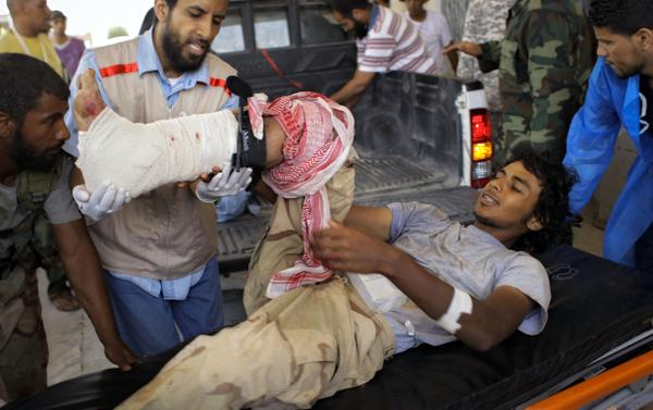 A wounded rebel fighter is transported from a pickup to the hospital in rebel-held Ajdabiya.