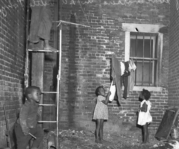 "The children of African American war workers play in a Little Tokyo alley. Little Tokyo in Los Angeles was dubbed ""Bronzeville"" during World War II, as African American families and workers moved into the empty homes and businesses of the relocated Japanese American community."