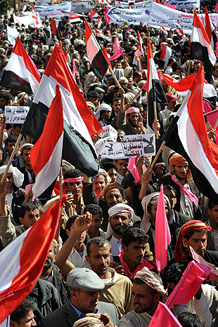 Protesters wave national flags during a protest in Yemen