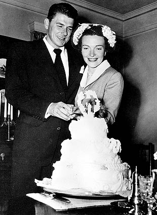 Newlyweds Ronald Reagan and Nancy Reagan cutting their wedding cake