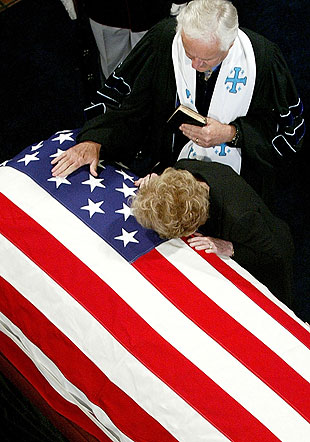 The Rev. Michael Wenning stands by as Nancy Reagan bends over the casket of her husband.