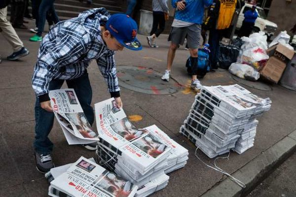 Passersby pick up the Occupied Wall Street Journal.