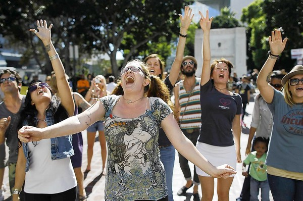 Lauren Rock of Los Angeles dances with dozens of other demonstrators as a band called the Mowglis performs on the steps of City Hall.