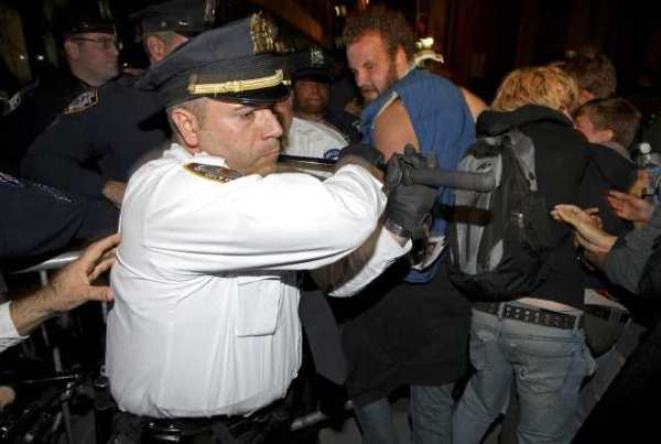 A police officer swings his baton to keep marchers behind barricades in Manhattan.