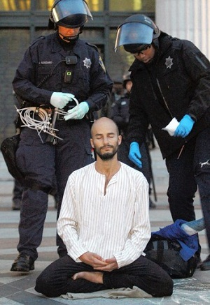 A protester meditates as police move to arrest him at Occupy Oakland. (Nov. 14, 2011)