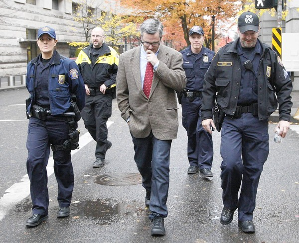 Portland Mayor Sam Adams, flanked by police as he walks to City Hall. (Nov. 14, 2011)