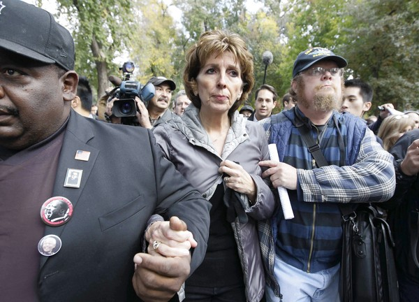 Linda Katehi is escorted from a small stage in the campus quad after she apologized to more than 1,000 students and faculty members.
