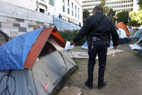 A general services officer hands out fliers letting Occupy L.A. campers know that they will no longer be allowed to stay overnight on the City Hall lawn. (Nov. 26, 2011)