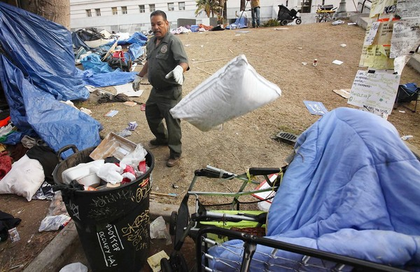 Sanitation worker Gino Ramirez starts clearing the debris left behind after the eviction of Occupy L.A. protesters. (Nov. 30, 2011)