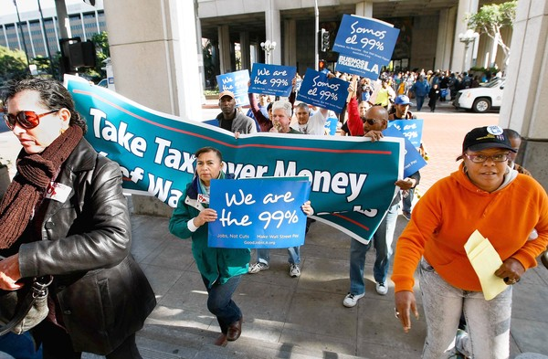 Occupy L.A. activists march toward City Hall to attend the budget and finance committee meeting after a rally supporting reforms in the city