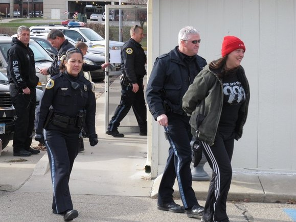 Julie Brown, 34, is escorted by police from the Iowa Democratic Party headquarters in Des Moines. (Dec. 19, 2011)