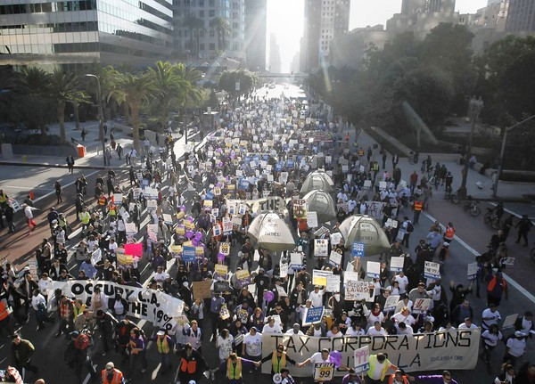 Demonstrators crowd onto a downtown Los Angeles street.
