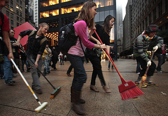 Protesters sweep the sidewalk in the financial district as part of a symbolic effort to clean up Wall Street.