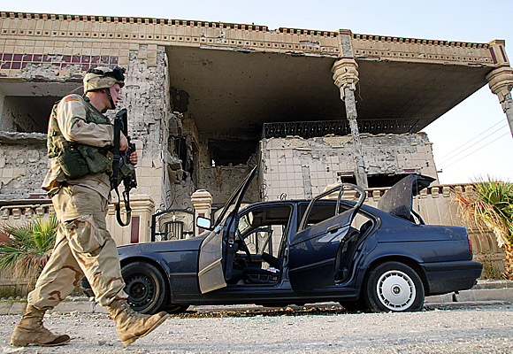 An American soldier stands guard outside the house in Mosul, Iraq, where Uday and Qusai Hussein were killed.
