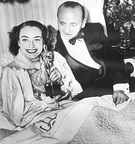 "Joan Crawford, too ill to attend the ceremonies, poses at home with her Oscar for ""Mildred Pierce"" and the film's director, Michael Curtiz."