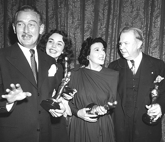 Paul Lukas, left, Jennifer Jones, Katina Paxinou and Charles Coburn pose backstage with their statuettes.