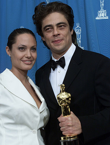 Presenter Angelina Jolie poses backstage with Benicio Del Toro.