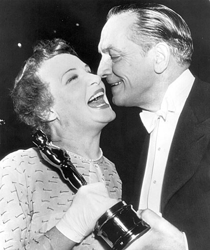 Shirley Booth laughs heartily as actor Fredric March prepares to give her a kiss on the cheek after she was presented with an Oscar.