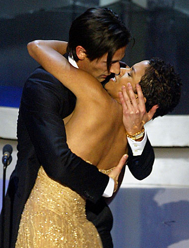 Adrien Brody surprises presenter Halle Berry with a kiss.