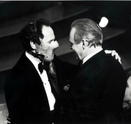 Billy Crystal, in a mask like Hannibal Lecter was forced to wear, greets Anthony Hopkins on stage.