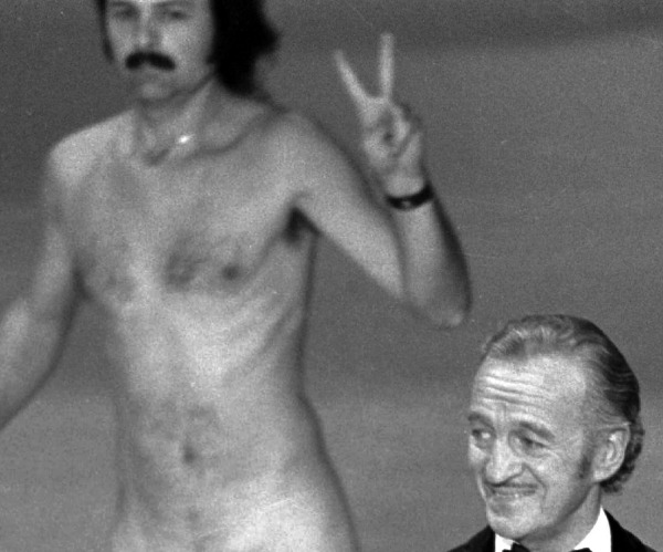 A man later identified as Robert Opel streaks behind host David Niven.