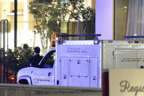 A Los Angeles police crime lab truck sits in the driveway of the Beverly Hilton Hotel.