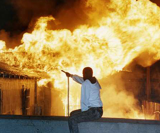 A resident vainly attempts to fight a raging fire at 79th Street and Normandie Avenue using a garden hose. (April 29, 1992)