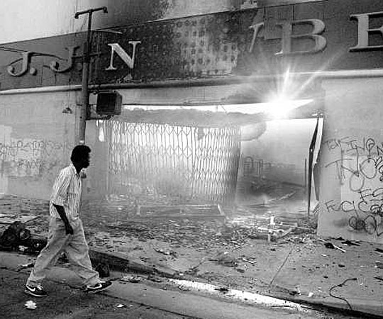 At sunrise, a lone pedestrian walks by burned-out shell of a J.J. Newberry building at Vermont Avenue near 59th Street. (April 30 1992)