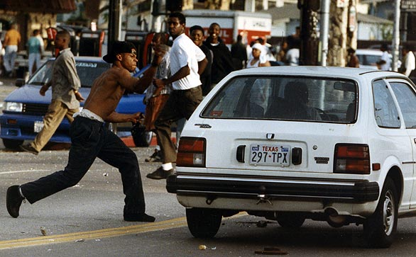 A rioter attacks a car on Florence and Normandie avenues. (April 29, 1992)