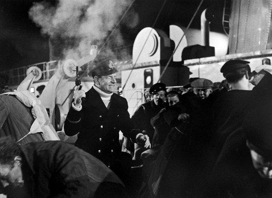 Actor Kenneth More, playing Second Officer Charles Herbert Lightoller, fires his pistol into the air in a scene from the 1958 film.