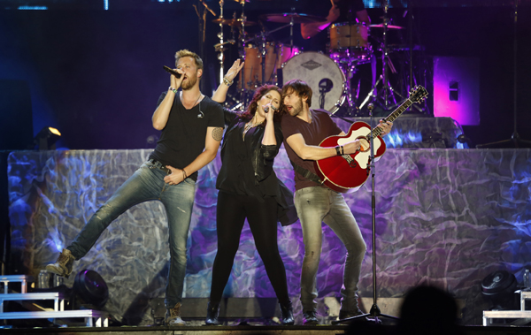 Lady Antebellum members Charles Kelley, lead vocals, left, Hillary Scott, lead vocals, and Dave Haywood, guitar and piano, and Chris Tyrell, drums, perform onstage.