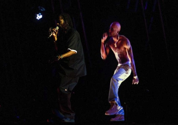 Snoop Dogg performs with an image of Tupac.