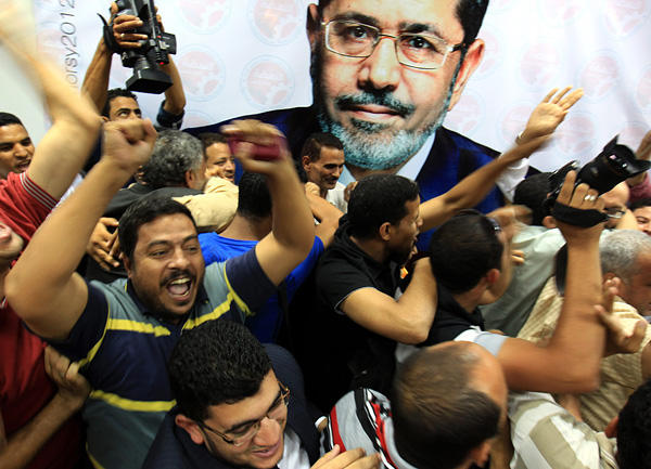 Members of the presidential election campaign of Muslim Brotherhood's Freedom and Justice Party candidate Mohamed Morsi, depicted in poster, celebrate upon the announcement of his victory in a historic election, at their headquarters in Cairo.
