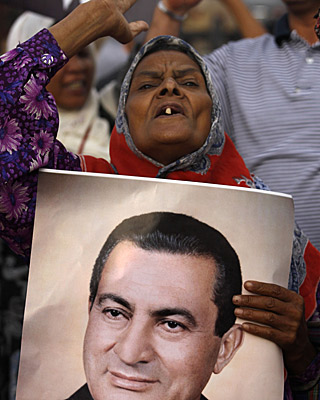 A woman holds a portrait of Hosni Mubarak outside the court