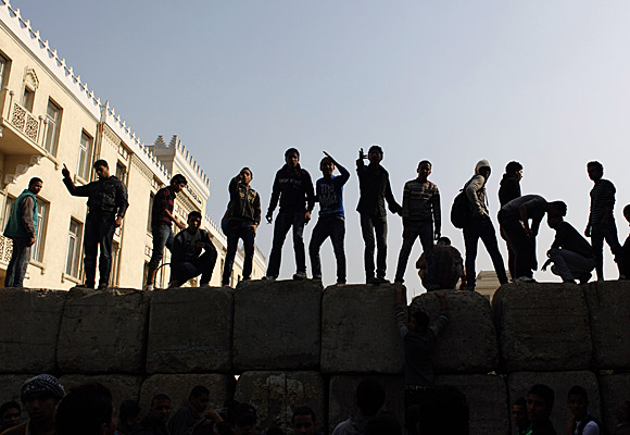 Protesters stand atop a barrier put up by the military to block a road near Tahrir Square in Cairo.