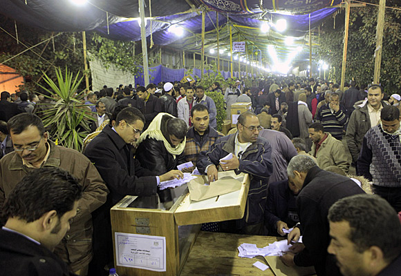 Egyptian election officials count votes in front of a ballot box at a counting center in Giza.