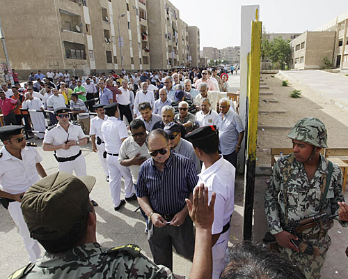 Egyptian army soldiers stand guard as hundreds of Egyptians line up outside a polling station in Cairo.