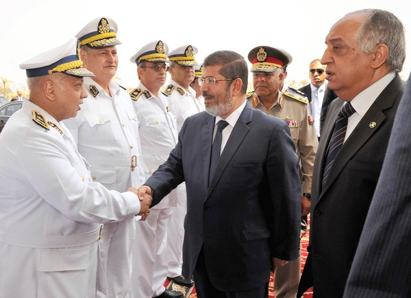 President-elect Mohamed Morsi, accompanied by Interior Minister Mohamed Ibrahim Youssef, right, meets with Egyptian police officers in Cairo.
