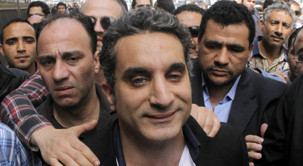 A bodyguard secures popular Egyptian television satirist Bassem Youssef, who has come to be known as Egypt's Jon Stewart, as he enters Egypt's state prosecutors office to face accusations.