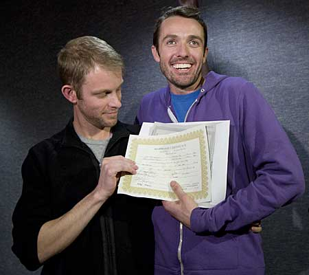 Seth Anderson, left, and Michael Ferguson, right, hold up their marriage certificate and license outside of the Salt Lake County Clerk's Office.