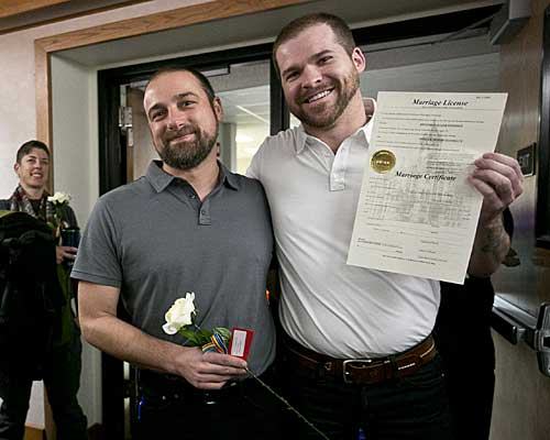 Patrick Donnelly, left, and his partner Ben Bahnsen pose with their marriage license at the Gallatin County Law and Justice Center in Bozeman, Mont.