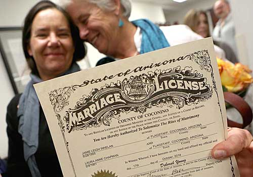 Laura Anne Chapman, left, and Jamie Whelan show their marriage certificate in Flagstaff, Ariz.
