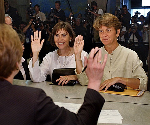 Hillary Goodridge, right, and Julie Goodridge, left, raise their right hands and affirm that everything on their marriage license is correct while at Boston City Hall.