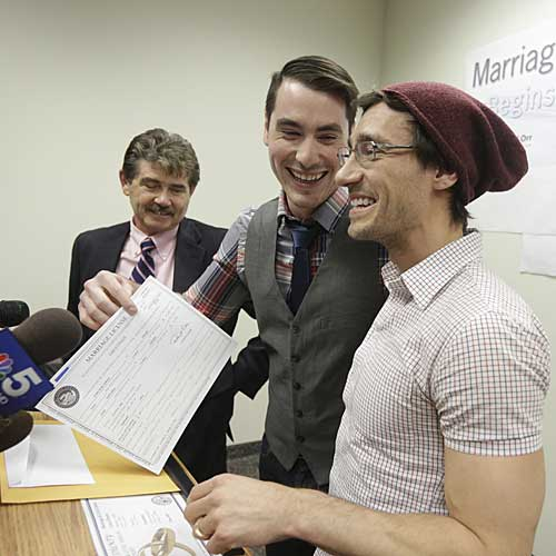 Charlie Gurion, center, and David Wilk hold up their marriage license as Cook County Clerk David Orr, left, looks on.