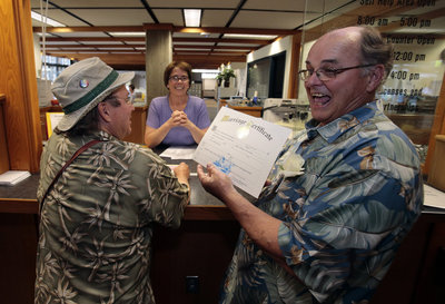 Bruce Carlson, right, shows off his ceremonial marriage license to wed his partner, Matt Friday, left, at the Lane County courthouse in Eugene, Ore.