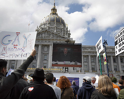 Supporters and foes of Proposition 8 watch a large-screen television outside San Francisco City Hall.