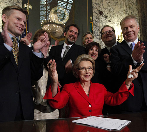 Gov. Chris Gregoire, seated, with legislators and supporters after signing a bill allowing gay marriage.