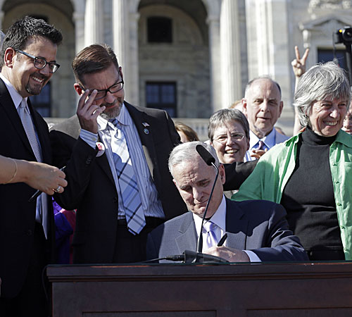 Minnesota Gov. Mark Dayton signs the gay marriage bill in front of the state Capitol. Sen. Scott Dibble, second from left, and Rep. Karen Clark, right, both gay lawmakers and sponsors of the bill, are among those watching the signing.