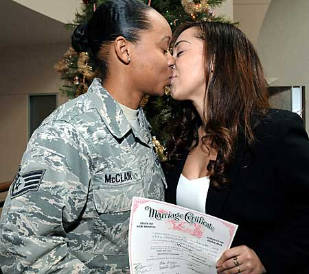 Staff Sgt. Aisha McClain, left, and Shannelle Williams kiss after getting married at the Doña Ana County Government Center.